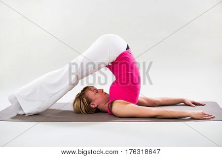 Photo of woman exercising yoga indoor-Plow pose/Halasana