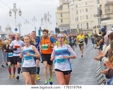BRIGHTON GREAT BRITAIN - FEB 26 2017: Two young woman and competitors running in the Vitality Brighton half marathon competition. February 26 2017 in Brighton Great Britain