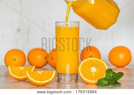 pouring the juice into a glass. orange juice in glasses at light wooden background.