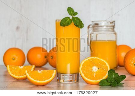 orange juice in glasses at light wooden background.