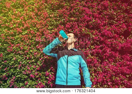 tired sweaty athletic sportsman drinking water in the park