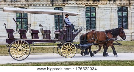ChambordFrance-September 082013: A carriage with a female coachman passing in front of the Chambord Castle. Chambord is royal medieval French castle in Loire Valley - UNESCO heritage site.