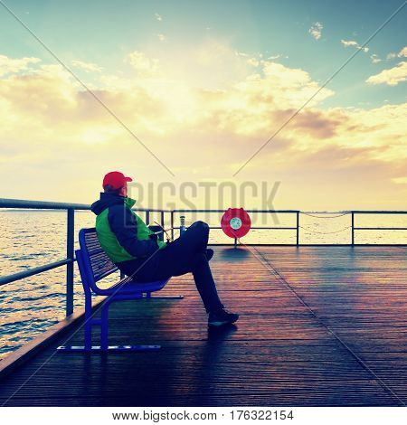 Man In Warm Jacket And Baseball Cap Sit On Mole Bench And Enjoy Morning At Sea.