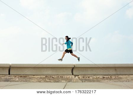 athletic sportsman running over concrete border near the ocean