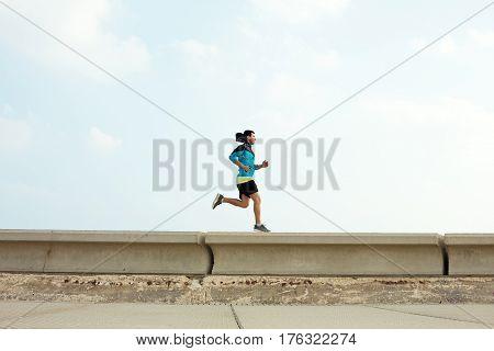 athletic sportsman running over concrete border near the ocean