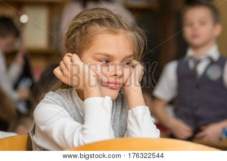 Girl Bored At School Sitting At A Desk On The Reverse