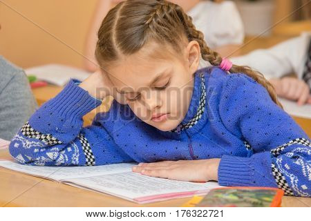 First Grader At Reading Lesson Reading Text Sitting At A School Desk