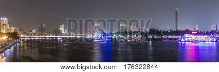 Panoramic view of Cairo city center at night the Kasr El Nile Bridge and the island of Zamalek with its colorful boats on the Nile river.
