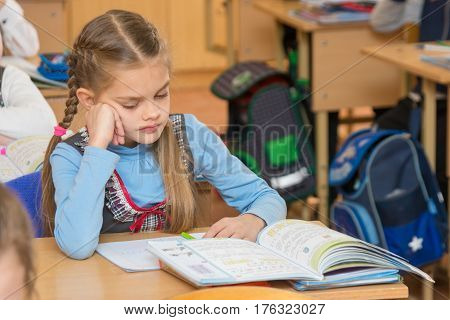 A Girl Pupil In The Classroom At School Looking At A Textbook