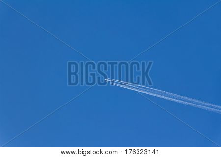 Airplane with contrails in clear blue sky