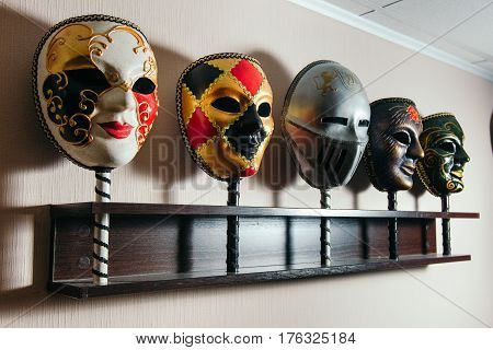 Masks for playing in the mafia stand on the shelf. Close-up.