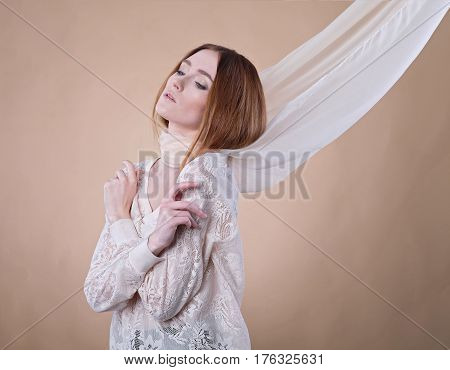 Young girl in shawl posing in studio on beige background. She dressed on translucent blouse. The light scarf on her neck twists in the wind. Her arms crossed near chest, eyes lowered.