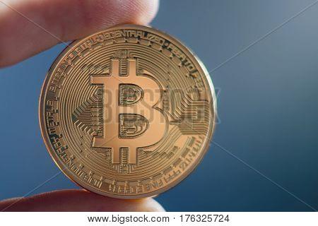 Hand holding golden Bitcoin virtual money.  Bitcoin cryptocurrency.