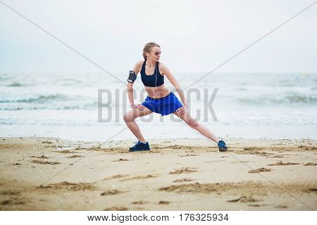 Woman On Beach Doing Stretching Exercise After A Workout