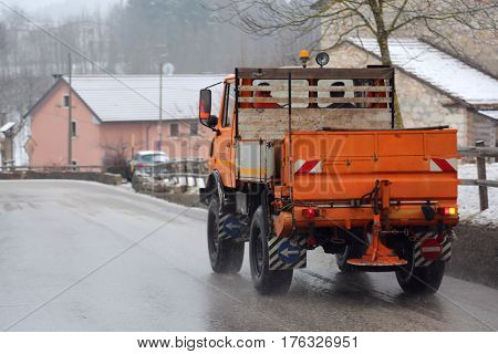 salt spreader on the street operating in winter