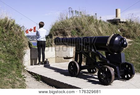 Halifax, Nova Scotia, September 23, 2015 -- Close up of a large iron canon pointing out towards the Halifax Harbor and a woman taking a photo of the city and Canadian flag blowing brightly on a bright sunny day in September