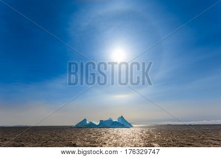 Sun Halo shining over the blue iceberg and ocean North Greenland