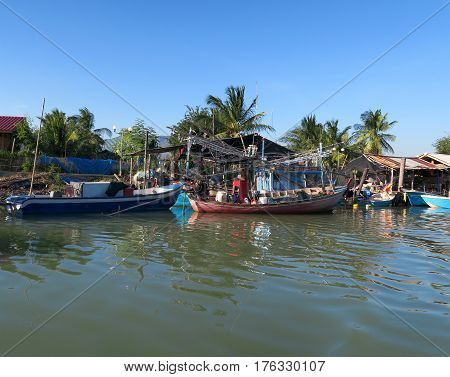 Some wooden fishing boats on front of a traditional village Thailand