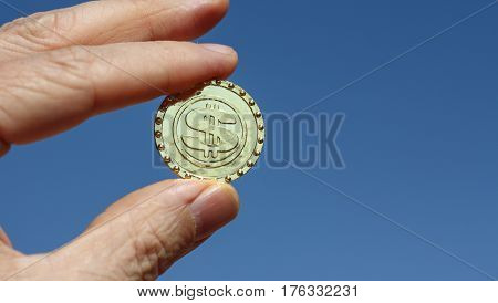 A newly minted bitcoin virtual currency unit held up to a blue sky