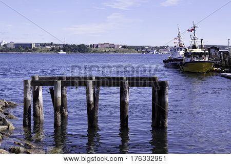 Halifax, Nova Scotia, September 23, 2015 -- An old wooden dock of pillars still stands in Halifax harbor with boats and buildings in the background on a bright sunny day in September