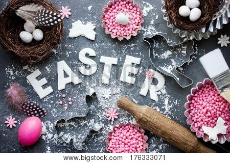 Easter festive baking background with Easter egg bird nest candy cookie cutter rolling pin on table with flour top view