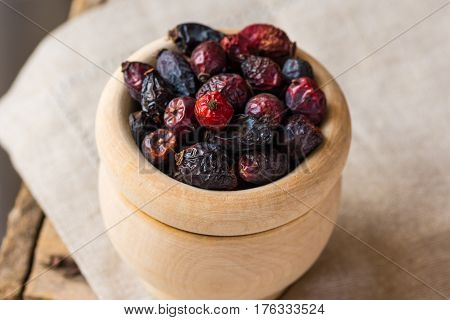 Dried rose hip berries in wood bowl on linen towel health concept natural medicine closeup soft colors top view