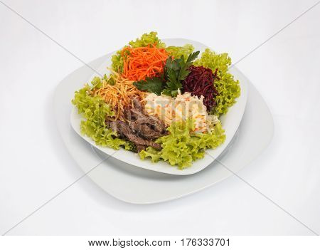 Fresh vegetable salad with slices of meat, filmed on a sheet of white plastic, close-up
