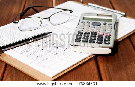 Accounting. Accountant. Accounting concept. Finance, financial analysis, accounting accounts spreadsheet with pen glasses and calculator on wood table. Business accounting and book keeping dates. Accountant of the firm.