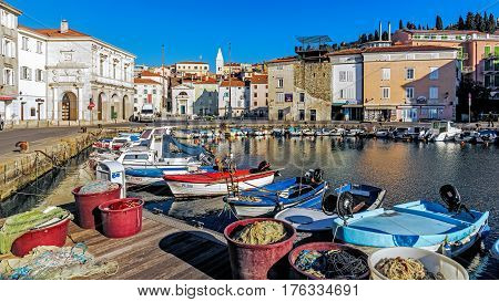 PIRAN, SLOVENIA - JANUARY 20, 2017: The fishery harbor of Piran, town on the Adriatic Sea, one of Slovenia's major tourist attractions with medieval architecture, narrow streets and compact houses.