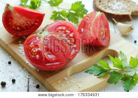 Cut fleshy and juicy tomato on a wooden board