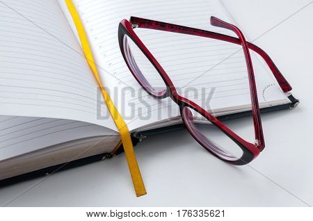 Red Glasses Lying On An Open Notebook With Bookmark