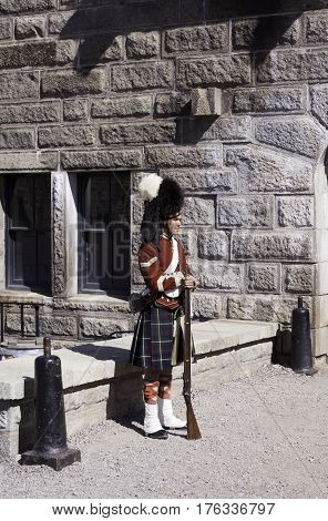 Halifax Nova Scotia September 23 2015 -- A single Highlander Guard stands sentinel beside a stone wall at the Citadel in Halifax Nova Scotia on a bright sunny day in September