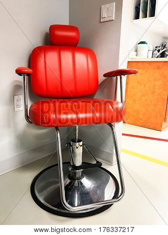 Old fashioned red leather examination chair with a hydrolic pump.