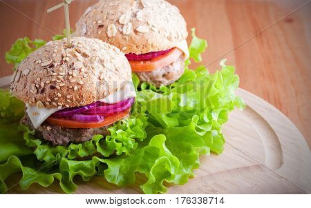 Cheeseburger with lettuce, onion and tomato on fresh bread.
