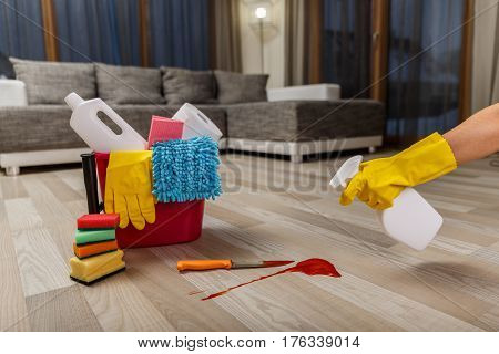 Crime cleaner concept. Bucket with sponges, chemicals bottles and plunger. Hand in rubber glove holding a spray. Paper towel. Knife and splash of blood.