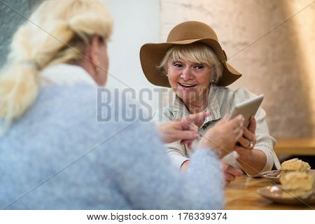 Elderly female with a tablet. Senior woman in cafe. Update os to latest version.