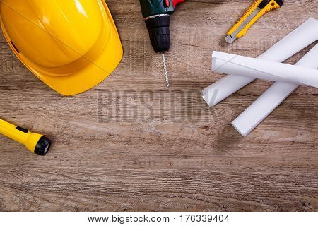 Yellow helmet, drill and flashlight. Construction concept. Architecture plans and knifes. Worker equipment. Engineering objects on workplace.
