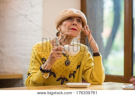 Elderly lady drinking coffee. Old woman with closed eyes. Focus and remember.