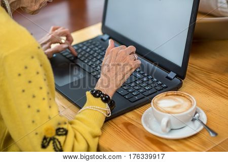 Senior female and laptop. White cup with coffee. Get familiar with new technologies.