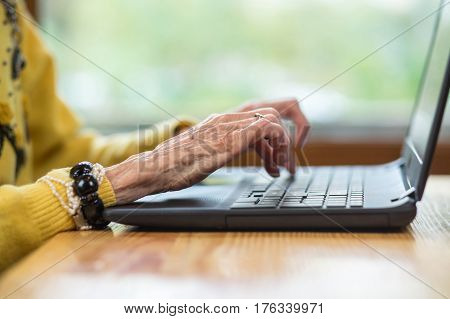 Laptop and elderly woman's hands. Notebook pc on blurred background. Get familiar with modern technologies.