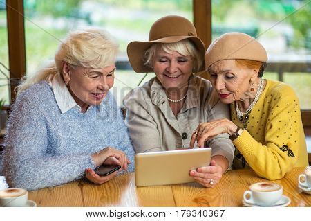 Senior women and tablet. Three ladies at cafe table. Find friends in social network.