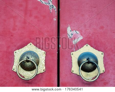 Closeup view of traditional Chinese red doors with metallic door knockers. This is an old specimen.
