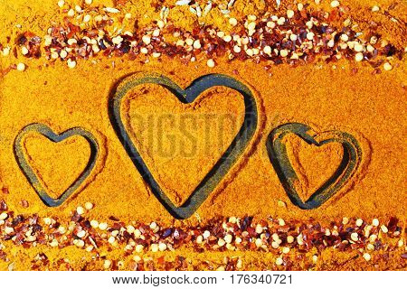 A background of turmeric powder and paprika powder with other spices and hearts in the center.