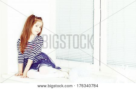 Little girl in blue striped dress and a white bow on her head.She sits at the window turned away from the camera.Creative toning of a photograph.