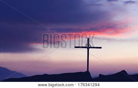 Christian cross over beautiful sunset background panoramic view