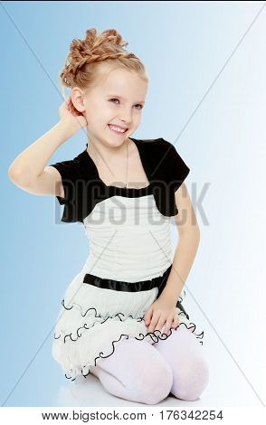 Beautiful little blonde girl dressed in a white short dress with black sleeves and a black belt.Girl stands on her knees and straightens her arm hair .On the pale blue background.