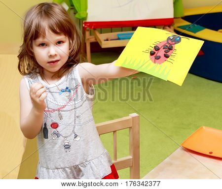 Joyful little girl in Montessori kindergarten shows the application she made in class .