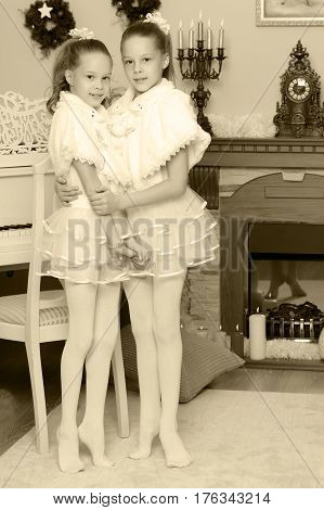 Little twin girls in beautiful white dresses hugging near the fireplace which burn Christmas candles.Black-and-white photo. Retro style.