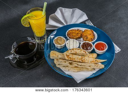 Oriental Indian Set,  Naan Bread And Onion Bhaji, Four Sauces, Blue Plate, Black Coffee, Orange Juic
