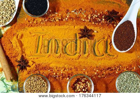 A board with ext India and turmeric and red chili powder with other spices like anise star methi seeds coriander seeds nigella seedss mustard seeds and fennel seeds top view.